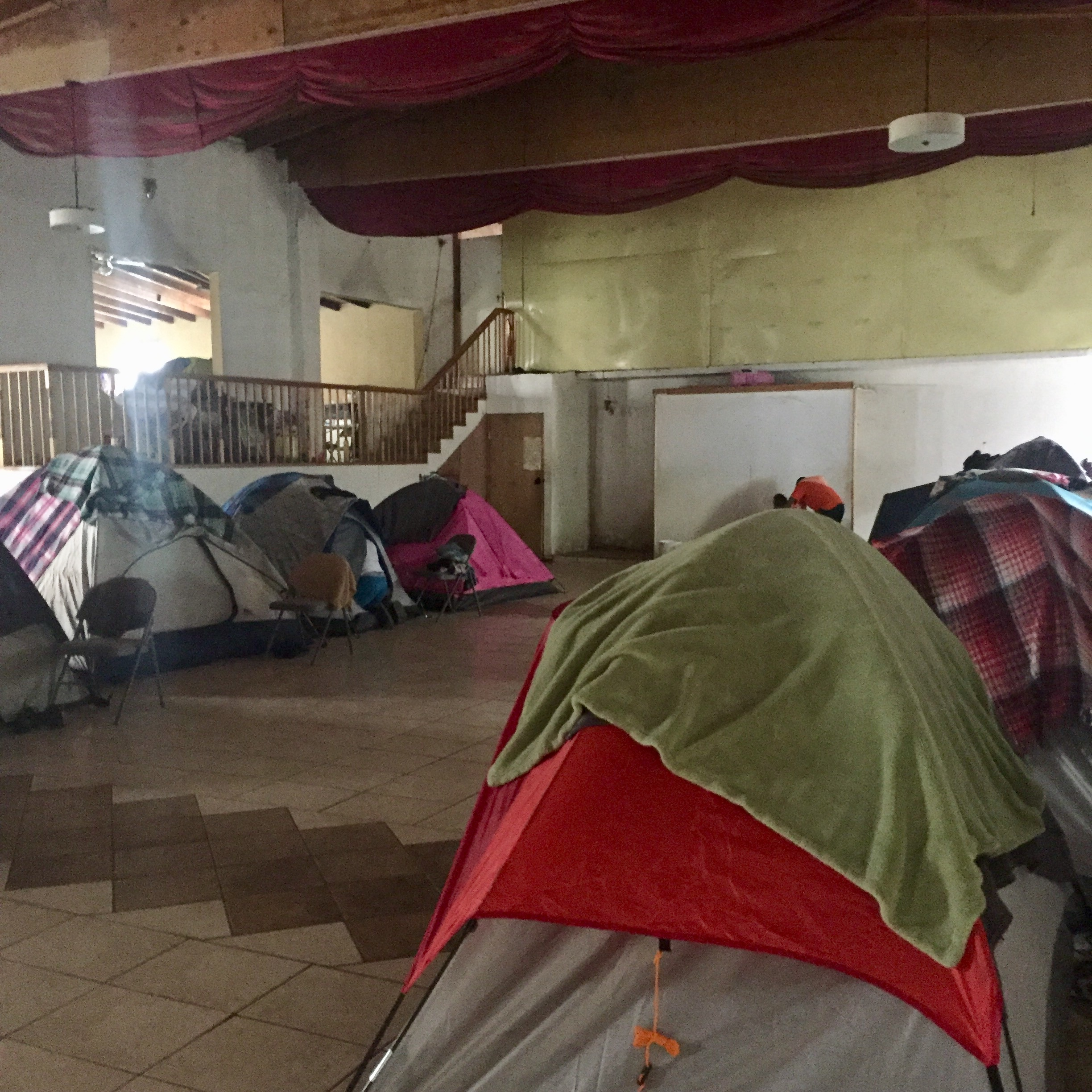 Tents provide individual family shelter inside a church.  Tents are set up throughout the church