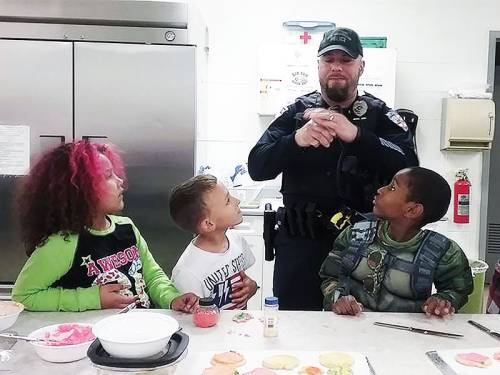 Children making cookies with a police officer