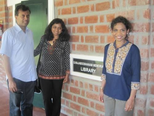 Photo of the writer with her sister and brother-in-law near the library plaque.