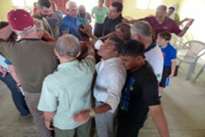 Hondurans and North Americans pray with a terminally ill pastor. (Photo by Tracey King-Ortega)
