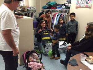 A clothes closet volunteer at Calvary Presbyterian Church offers a Batman shirt to a young boy