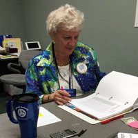 Deb DeMeester, director of leadership development for the Synod of Lakes and Prairies, works the desk in the Synod School office. (Photo by Duane Sweep)