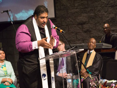 The Rev. Dr. William Barber II preaches at St. Stephen Baptist Church in Louisville during the October 4 'Moral Revival'. The Rev. Dr. James Forbes is seated, wearing stole. (Photo by Gregg Brekke)