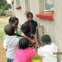 Children gather water at one of the school's taps. (Photo by Talkmore Chilanga)