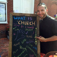 Rev. Fernando Rodríguez Quiñones displays a sign with responses from Peach Festival attendees.