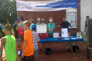 Volunteers at the Church on Main sell water and distribute information during the Peach Festival.