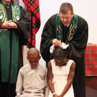 Rev. John Odom baptizes Marceline Kilassa and Benjamin Kibfoulwa, with Rev. Kathryn Campbell. Both children received help through the Black Child Development Institute.