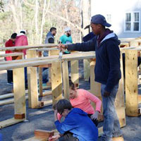 Members of Hartford Street Presbyterian Church, St. James Episcopal Church, and Temple Israel in Natick, Massachusetts, along with the Islamic Society of Framingham, apply seal coating to garden beds to be used in the Natick Community Garden, on the grounds of Hartford Street Presbyterian Church. (Photo by Michael Fitzgerald)