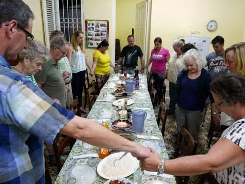 Mission partners from the Presbytery of Long Island and Güines Church in Cuba offer a blessing before they share a meal at the manse of the Cuban church. (Photo courtesy of Barbara D'Andrea)