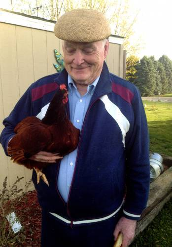 Rex Wentzel with one of his Rhode Island Red chickens.