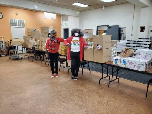 three women standing with food distribution boxes