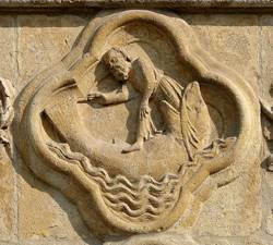 A carving of the Biblical story Jonah and the whale in light brown stone.