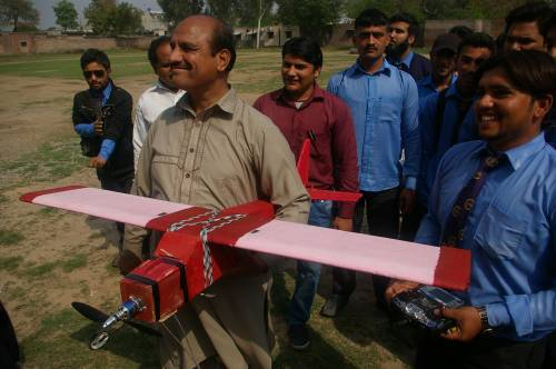 Electronics professor with students proudly showing their project, a remote control airplane