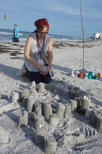 Angie Andriot of Research Services for the Presbyterian Mission Agency, creates a sand castle at the Building Station. Photo by Mari Graham.