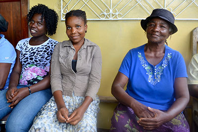 Marie Sylvie Pierre, right, her daughter, Delphine Pinette, center, and Darline Mettra listen during an Oct. 5 meeting with local grassroots farmer organizations, a delegation from Presbytery of the James, and coordinators of a Presbyterian Disaster Assistance grant helping people in the South of Haiti affected by Hurricane Matthew in October 2016.