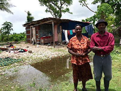 Marie Silvie Pierre and Pinette Tolerme stand in front of their home in Torbeck, Haiti. The effects of Hurricane Matthew remain in this community, seven months after striking the southern coast of Haiti. (Photo by Cindy Corell)