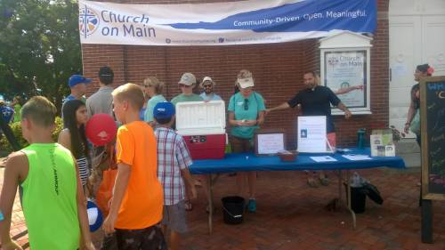 Volunteers at the Church on Main sell water and distribute information during the Aug. 20 Peach Festival (Photo provided)