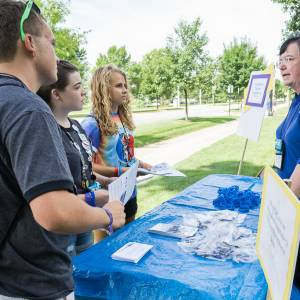 Students from Peaks and Prairies and Chicago presbyteries, Eli, Abby and Hannah, speak with Beth Snyder of Presbyterian Disaster Assistance during the Triennium advocacy walk. (Photo by Gregg Brekke)