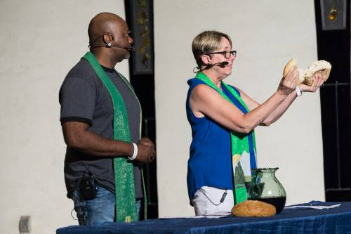 Perryn Rice and Jan Edmiston serve communion at the Friday evening worships service of the 2016 Presbyterian Youth Triennium. (Photo by Gregg Brekke)