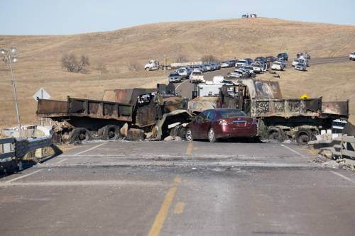 Two burned out trucks and a crashed car block the north end of Backwater Bridge on North Dakota highway 1806. (Photo by Gregg Brekke)