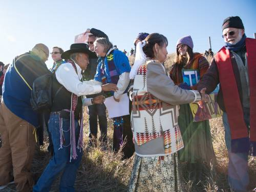 Sara Lisherness, director of Compassion Peace and Justice ministries at the PC(USA), are greeted in the Niobrara Circle ceremony. Also pictured is Rick Ufford-Chase. (Photo by Gregg Brekke)
