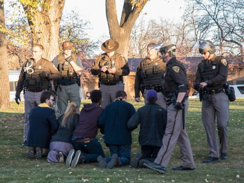 Zebulon Armstrong-Green, Alison Harrington, Anthony Grimes, Rick Ufford-Chase and Tithe Barry kneel before their arrest on the lawn outide North Dakota governor Jack Dalrymple's residence. (Photo by Gregg Brekke)