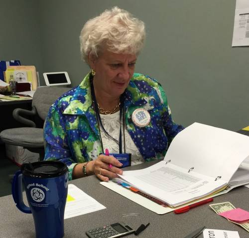 Deb DeMeester, director of leadership development for the Synod of Lakes and Prairies, works the desk in the Synod School office. Photo by Duane Sweep.
