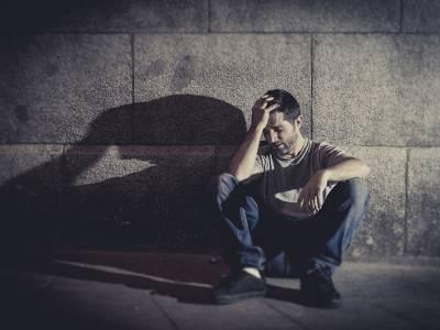 depressed man sitting on street ground with shadow