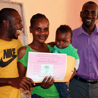 Herve Delisma (left), the assistant coordinator of the MPP-FONDAMA Yard Garden Program, and Viljean Louis (right), the coordinator for the Farmer Movement of Bayonnais, presenting a certificate of achievement to Aliette Baptiste, from the community of Demòn, for the excellent development of her yard garden.