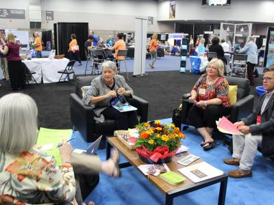 The Rev. Jean Dow (center) leads an informal discussion in the Exhibit Hall at General Assembly about a campaign to reach out to gun manufacturers. Photo by Rick Jones.
