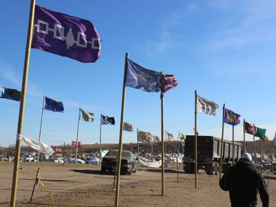 Tribal flags at At Oceti Sakowin Camp show the strength of the winter winds as they begin to move into the area. (Photo by Rick Jones)