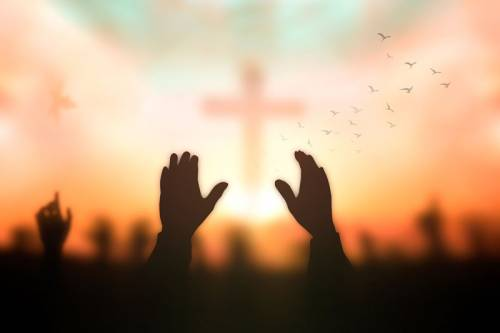 Photo of 2 hands upraised towards a cross