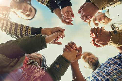Photo of a group of people standing in a circle, holding hands.