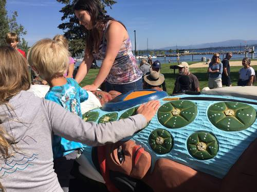 Residents of Sandpoint, Idaho get see and touch the 22-foot totem pole during a gathering on Sunday. (Photo by Susan Drumheller)