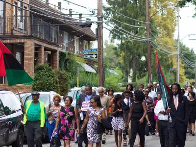 Dina 'Free' Blackwell leads a freedom march through the Homewood neighborhood of Pittsburgh prior to her husband's funeral service. (Photo by Susan Washburn)