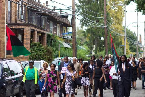 Dina 'Free' Blackwell leads a freedom march through the Homewood neighborhood of Pittsburgh prior to her husband's funeral service. (Photo by Abby Thornton)