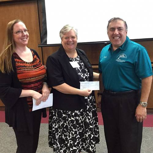 Pastor Nancy Jo Dederer (center) receives a $1,000 check to from the Homewood Area Chamber of Commerce. Chamber president Jen Sjoblom and Golf Outing Chair Nick Markioni presented the check to help fund the church's community dinners. (Photo by Geoff Slawson)