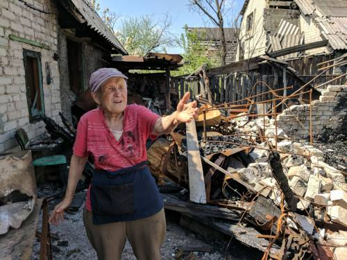 Ukrainian woman stands in rubble outside her damaged house