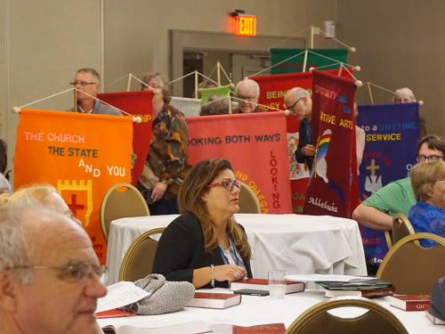 Conference participants parade into the gathering with a colorful procession of banners. (Photo by Emily Enders Odom)
