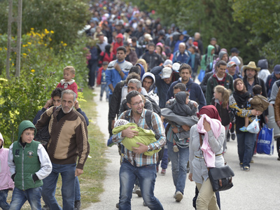 Refugees and migrants walk through the Hungarian town of Hegyeshalom on their way to the border where they will cross into Austria. Hundreds of thousands of refugees and migrants flowed through Hungary in 2015, on their way from Syria, Iraq and other countries to western Europe. The ACT Alliance has provided critical support for refugee and migrant families here and in other places along their journey. (Photo by Paul Jeffrey)