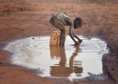 A girl fills a container with muddy water in the Ajuong Thok Refugee Camp in South Sudan. (Photo by Paul Jeffrey/ACT)