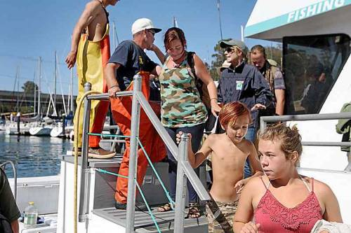 People step off a charter boat last Monday after a day of fishing on the bay thanks to the Christian group Sweaty Sheep who chartered the boat for two dozen homeless. (Photo by Dan Coyro, Santa Cruz Sentinel)