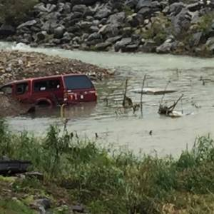 A pickup truck is left partially submerged in the aftermath of flooding in West Virginia. (Photo by Phillip Darby)