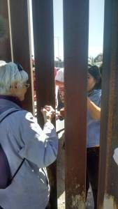 Mary and Cindy sharing bread through the wall at the Agape Feast