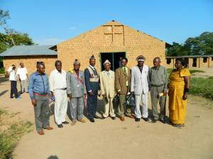 Pastor Christine standing with village chiefs at a promotion for marriage licensing