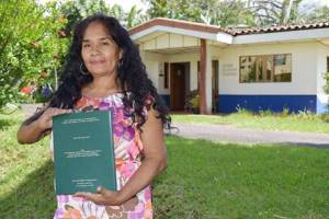 Rosemary Lopez with her master's thesis on women living with HIV