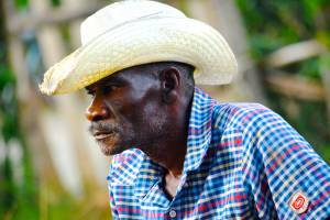 A farmer listens as his neighbors tell of being pushed from their land in Northeast Haiti