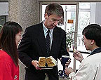 Photo of a man holding Communion bread and a cup and two other people.