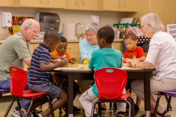 Volunteers from First Presbyterian Church and Altrusa Service Organization work with boys in the DREAAM House Summer Pre-K Academy. (Photo by Jay Schubert)