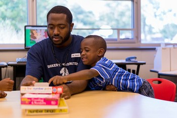Jason Knight, a DREAAM Achievement Coach, works with a student (Photo by Jay Schubert)